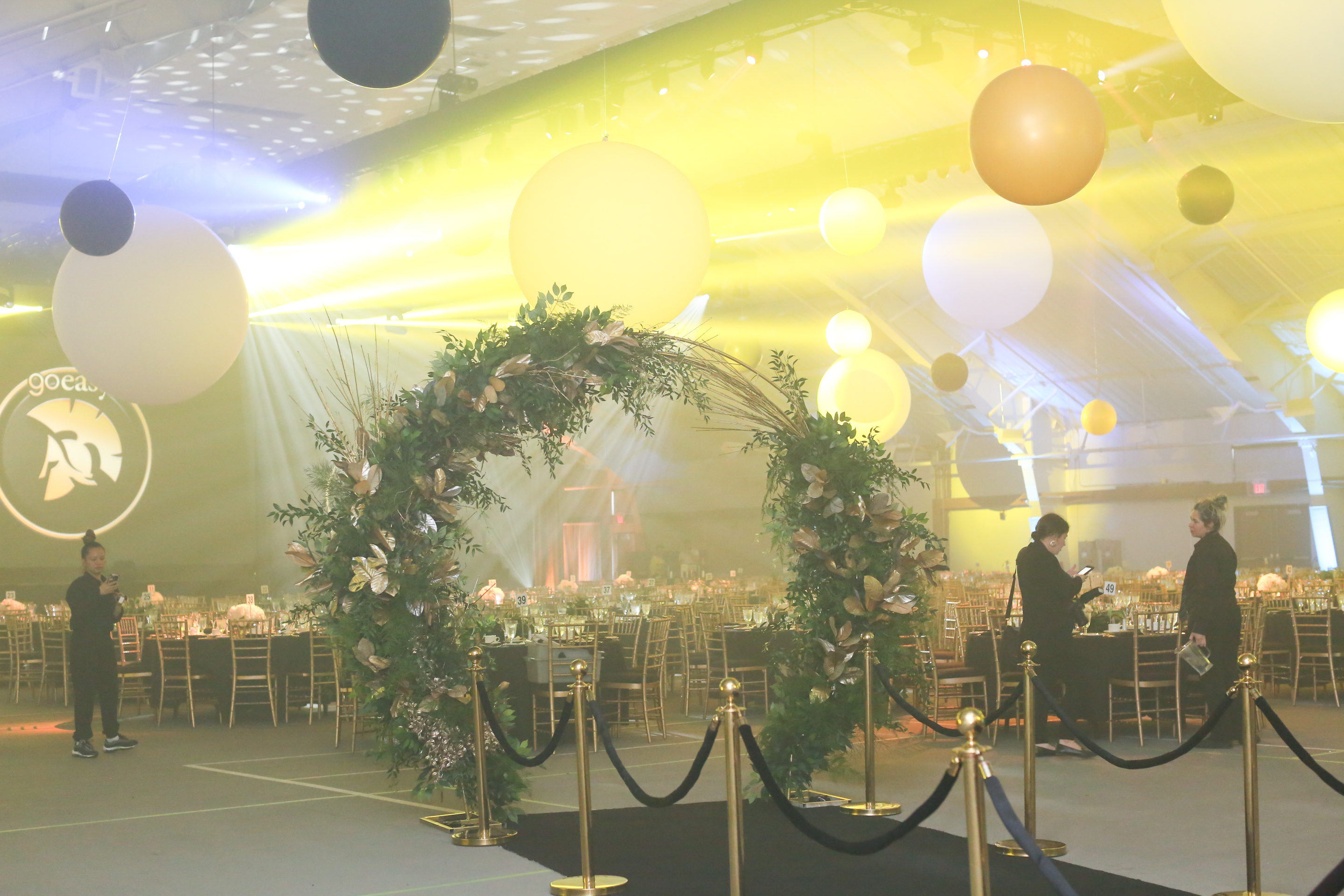 black and gold arch greenery floral gala event